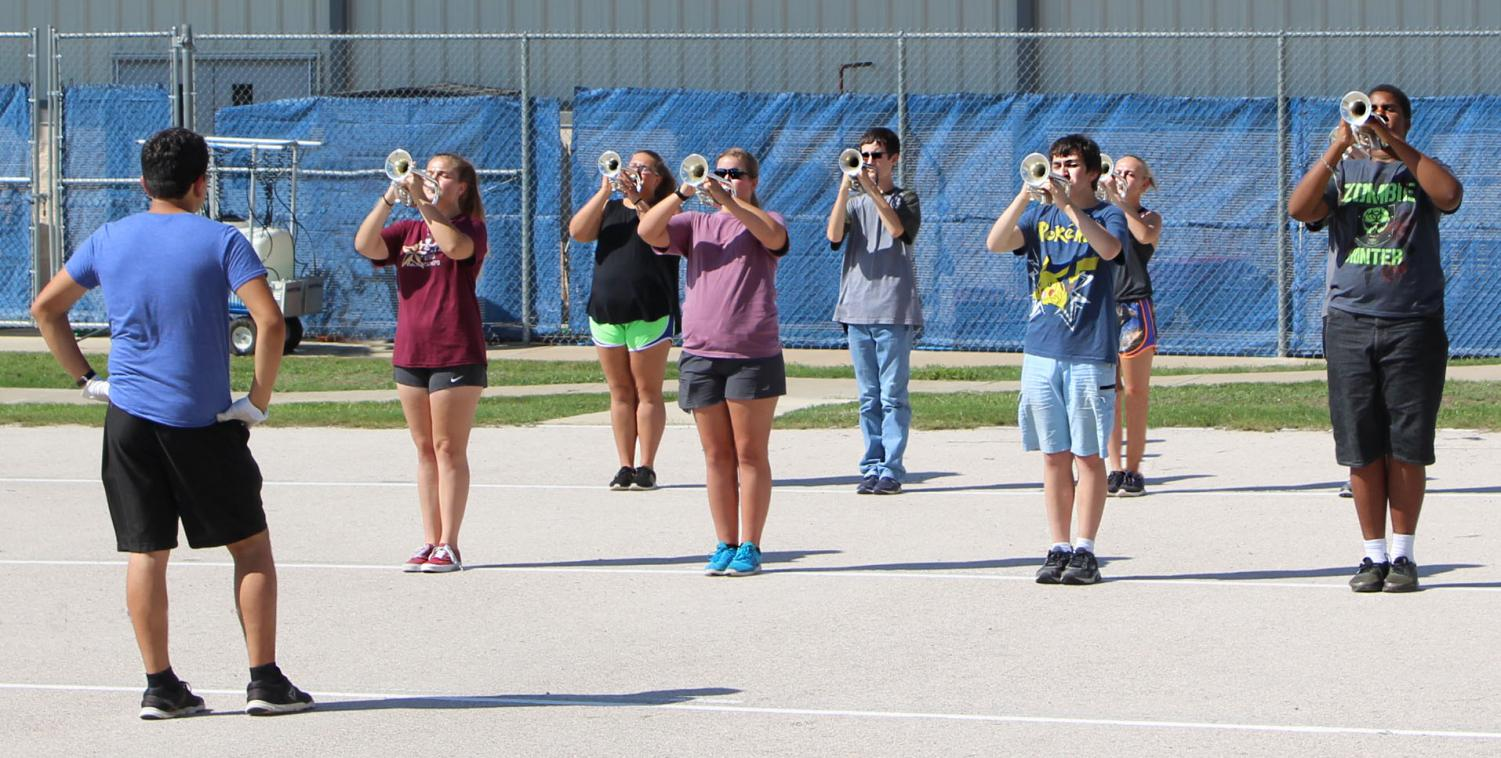 Drum major and junior Miguel Cazares leads band members as they practice for this year's field show,
