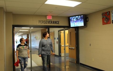 Students look at a picture from a cross country meet as they walk by a new TV in the upstairs hallway. The new TVs display pictures and videos from recent events.
