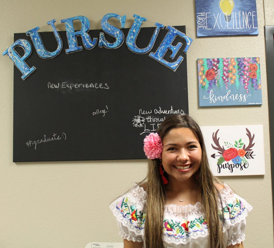 Senior+Monica+Garza+has+turned+her+passion+for+art+and+calligraphy+into+a+business+opportunity+by+creating+custom+paintings+for+customers.+Here%2C+she+stands+in+front+of+a+%22kindness%22+painting+on+Ms.+Shropshire%27s+word+art+wall.+