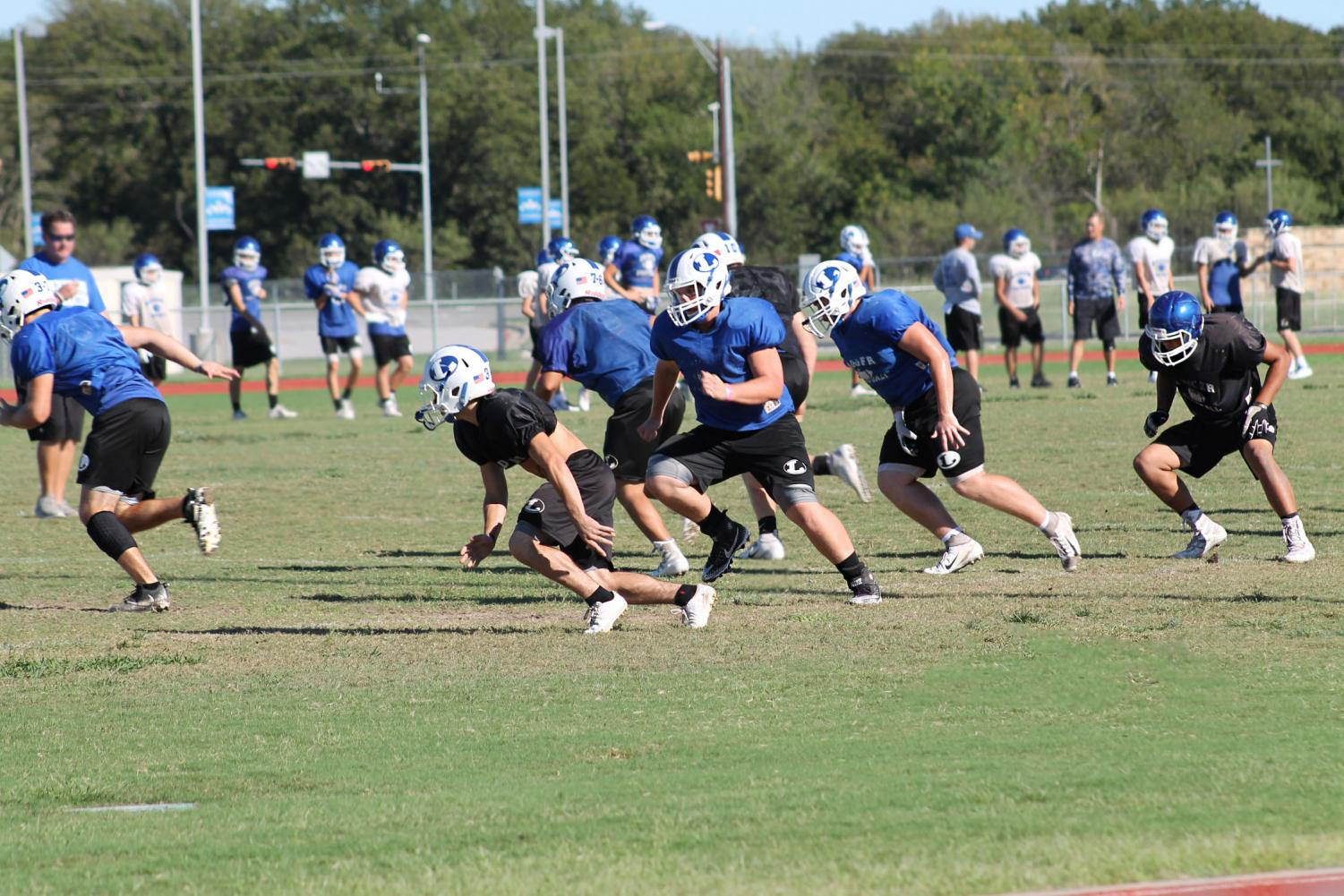 Varsity and JV football players practice after school on  Oct. 10 as they prepare for the  first district game of the year.