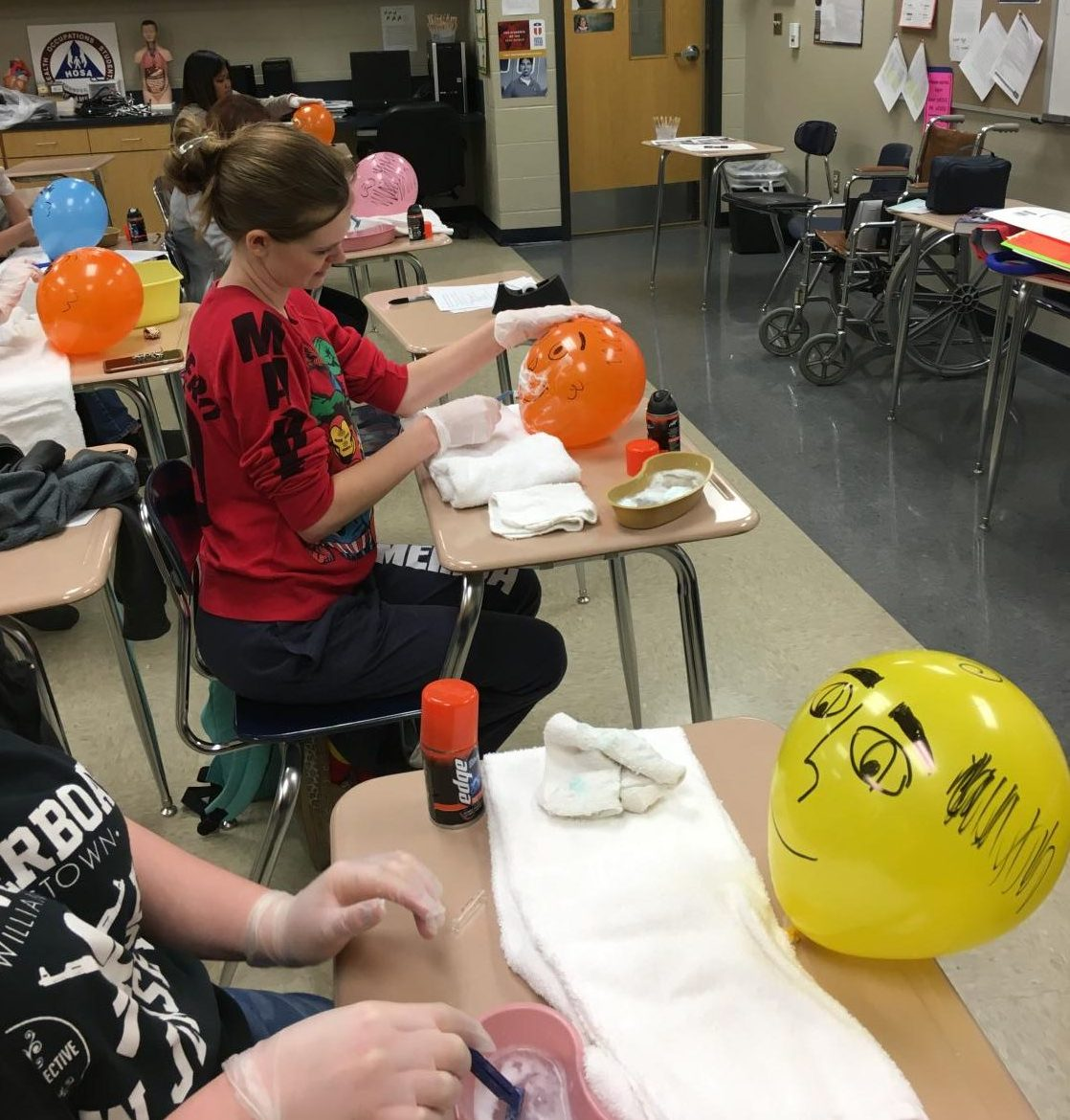 Students in Kerry Hammets CNA class practice shaving gently on balloons before visiting Spring Oaks Nursing Home to assist residents.