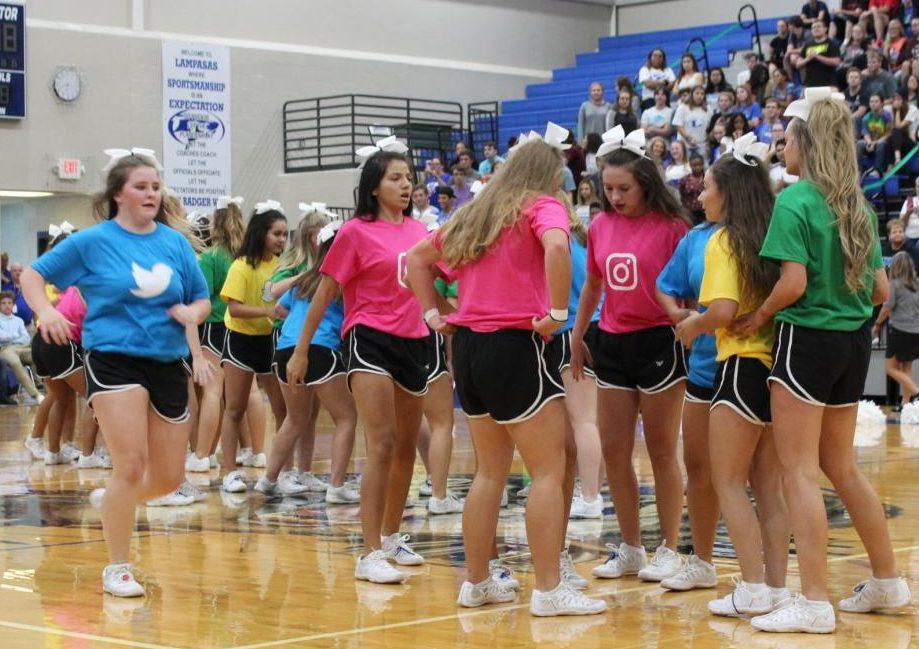 Freshman cheerleaders prepare a stunt alongside upperclassmen cheerleaders during their first high school pep rally.