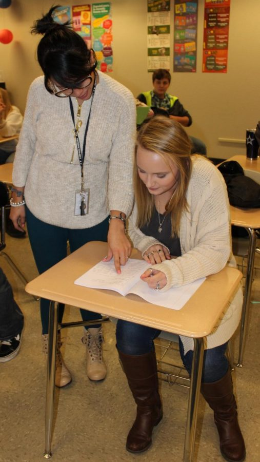 New Spanish teacher Elizabeth Santiago, from Puerto Rico, helps sophomore Harley Crumley on an assignment.