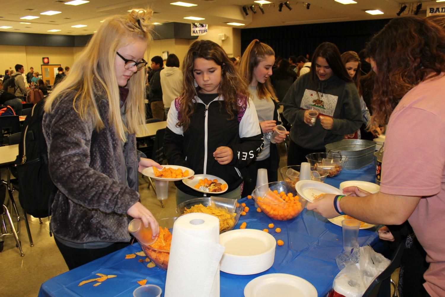 Freshman Emma Goodart grabs some snacks with friends during the Link Crew celebration Nov. 13.