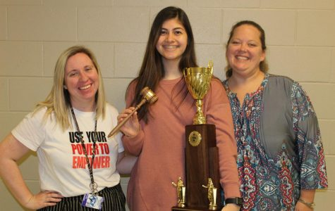Senior Sena Kucukkarca holds her first place award from the TFA state debate competition alongside her coaches Shelby Randolph and Judith Ann McGhee.