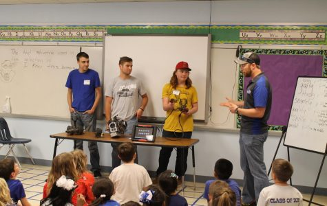 Mr. Gold and senior Zach tell the elementary students how the computers in automobiles work.