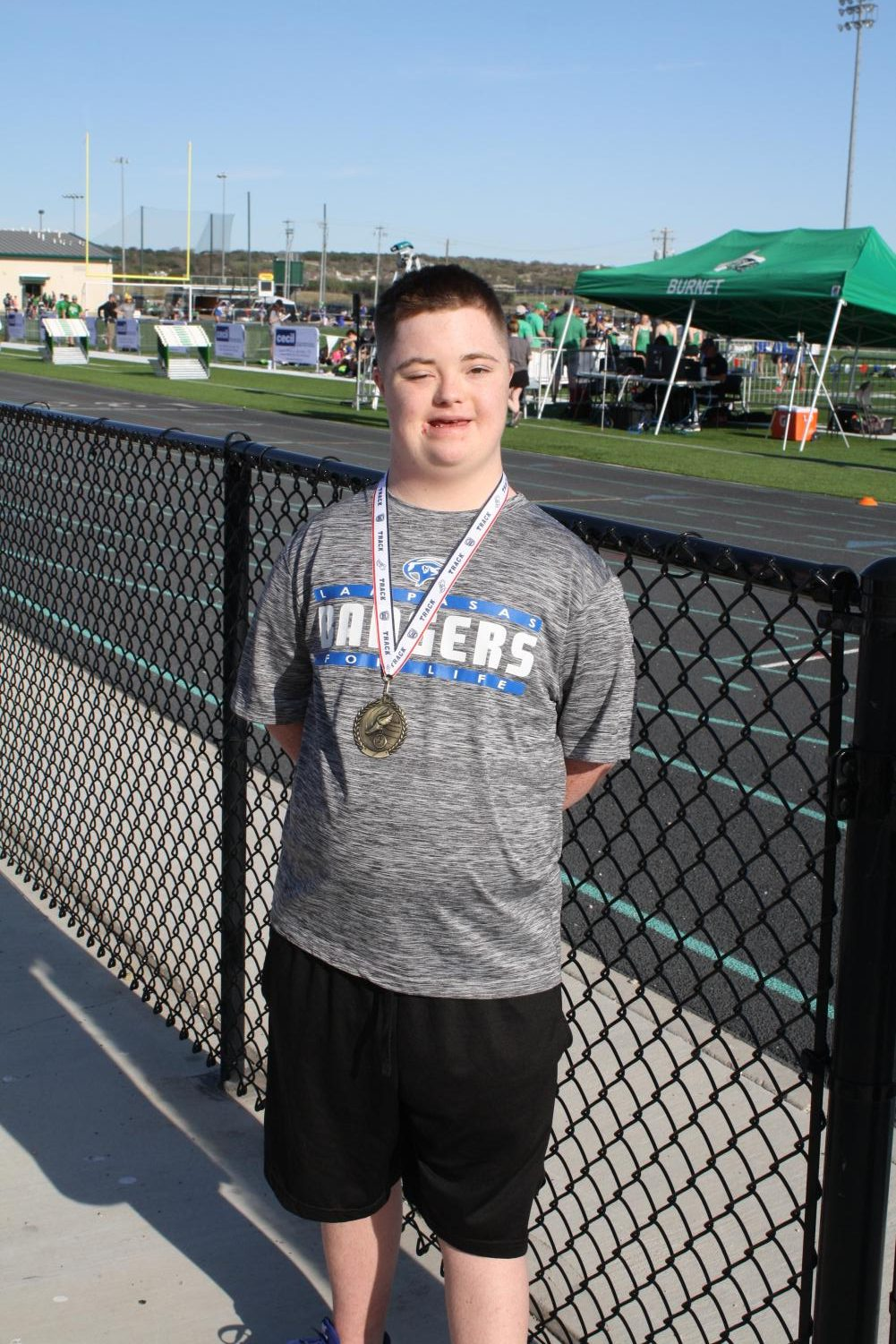 Life skills student Phillip Hallahan smiles with his medal after running   The Hundred Meter Special Race at the Burnet track meet on March 21.
