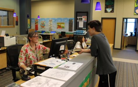 Assistant librarian Sarah Cimino receives a late book from sophomore Aiden Freas.