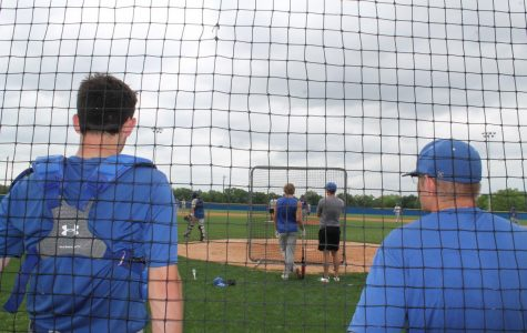 Juniors Haydn Hammerschmidt and Austin Hilgenberg stand on the sidelines while sophomore Ace Whitehead waits to bat during baseball practice.