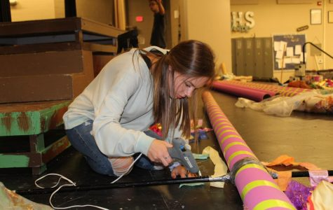Theatre secretary and stage manager Julia Hairston glues together a tree for the Seussical: The Musical set design.