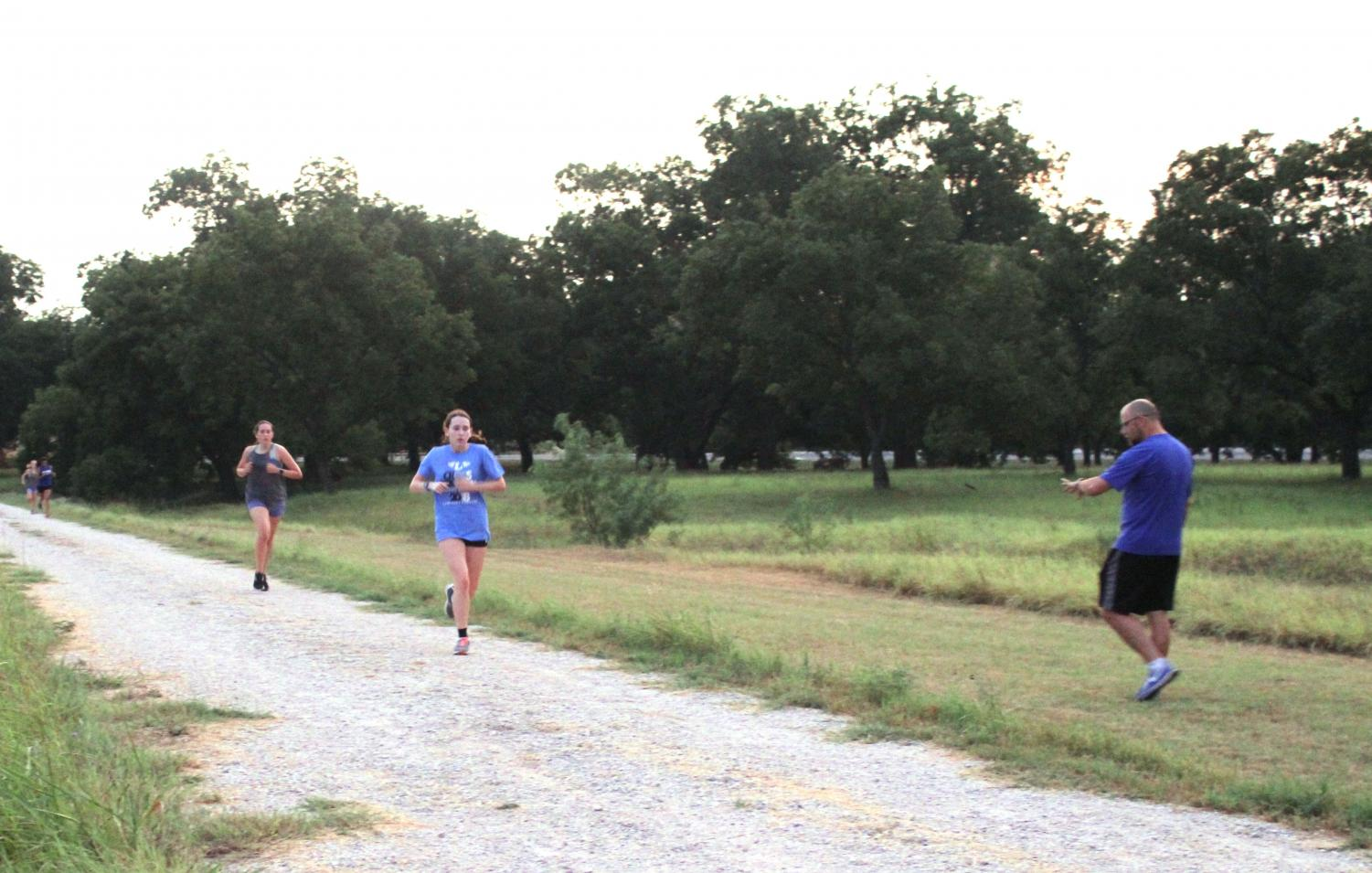 Head cross country coach Kiff Weimers times runners during morning practice.