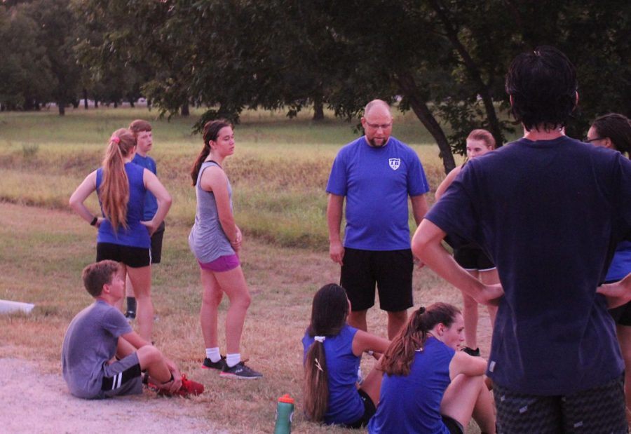 New cross country coach Kiff Weimers speaks with the team during morning practice.