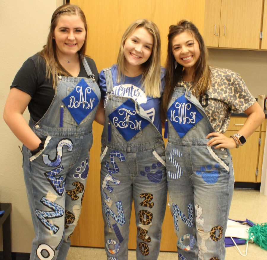 Seniors Destiney Nobles, Cami Ford and  Holley Wright wear overalls they decorated together. They are three of the cheerleaders hoping this will become a new senior tradition.