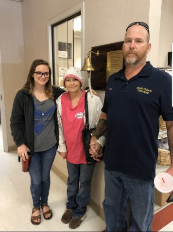 Junior Jalena Rostad stands with her mother Julie Bass-Smith and stepfather Fred Smith after Bass-Smith rang the bell signifying her final chemotherapy treatment.