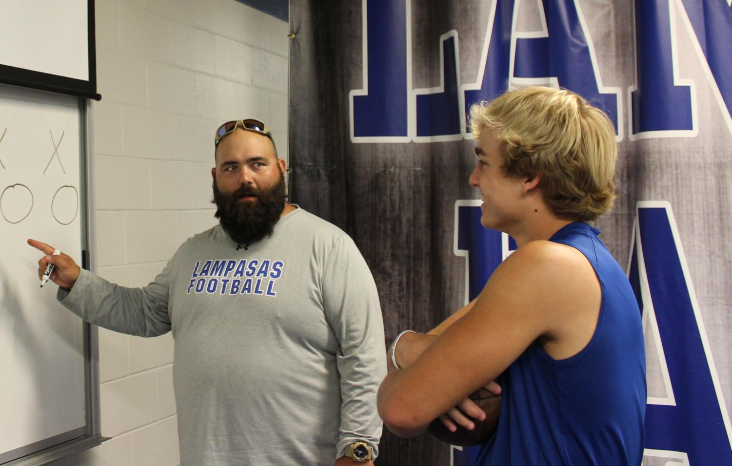 Football coach Tyler Cleavinger discusses plays with quarterback Ace Whitehead before the Taylor game.