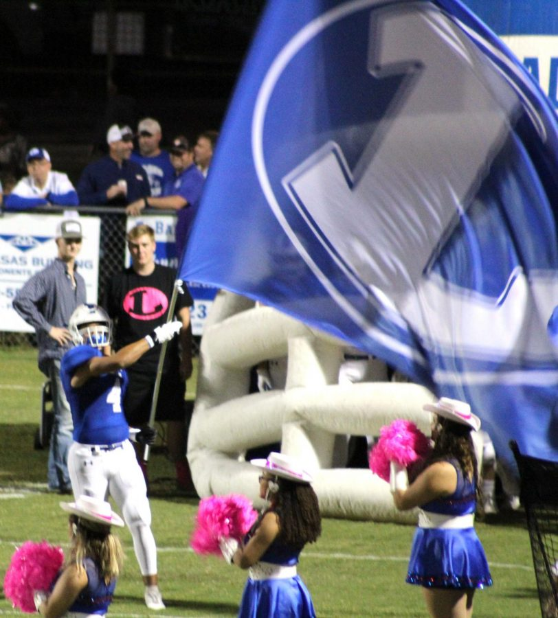 Senior Ethan Rascoe waves the Badger flag while leading the football team onto the field to face Liberty Hill on Friday. The Badgers won the game 52-10.