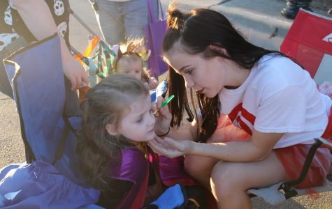 Flames social leader vice president Christina Dobbertin paints a child's face during Squared Silly on Oct. 26.
