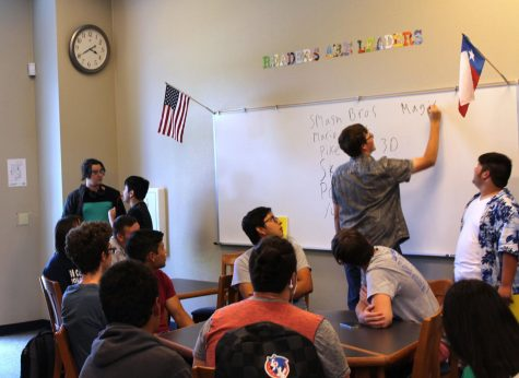 Senior Morgan Dandley listing game options on the whiteboard in the library on Sept. 25 during The Gaming Club.
