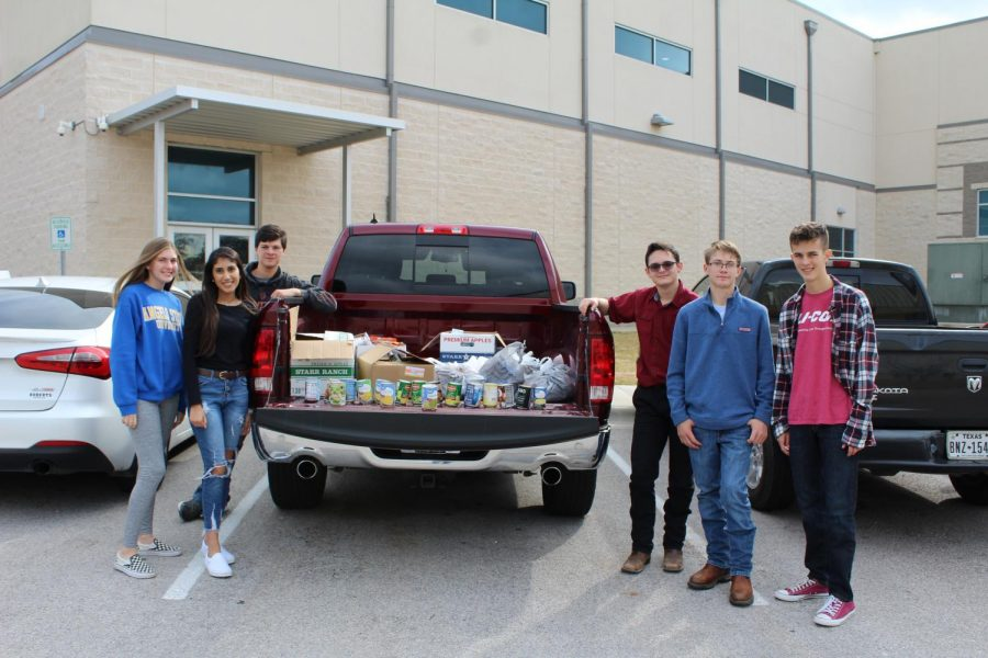 Student Council members with items collected from the annual food drive competition to support the Lampasas Mission.