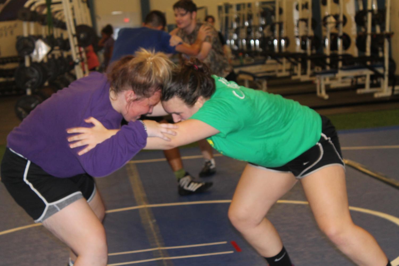 Juniors Gavin Robinson, Jonathon Dill, Taylor Talbert and Mia Martell practice stances during wrestling practice.
