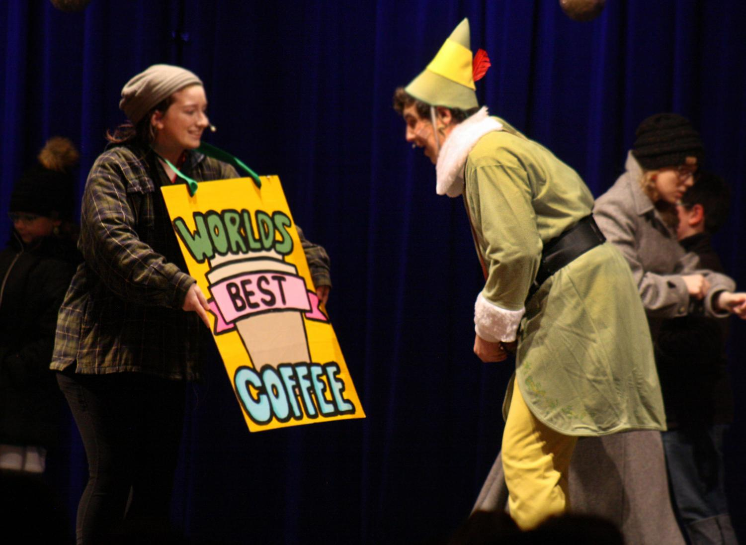 Freshman Kaitie McClendon holds a sign in front of junior Cole Wheeler during Elf The Musical.