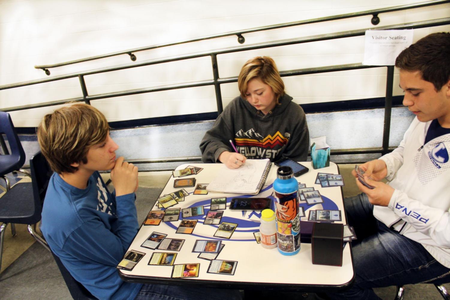 Freshman Brad Roberts, sophomore Shyla Roberts and sophomore Anthony Pena play Magic The Gathering during lunch Feb. 5. They will participate in the tournament in the library Feb. 12.