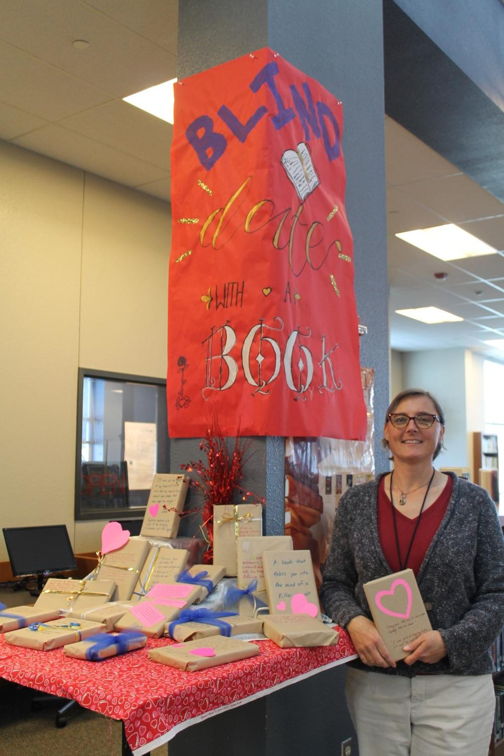 Assistant librarian Sarah Cimino holds one of the wrapped books for