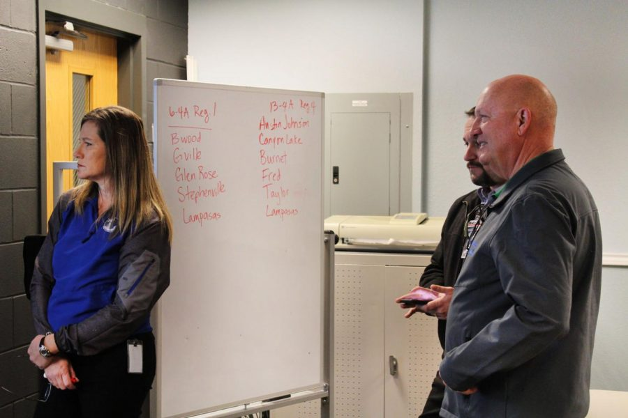 Head of athletic training Jan Brister, assistant superintendent Kevin Bott and Principal Joey McQueen study the UIL realignment projected in the Maker Space Feb. 3.