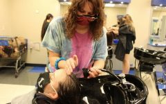 Senior Jalena Rostad washes another student's hair during advanced cosmetology class.