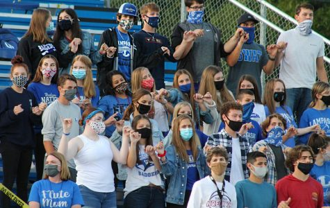 Students sing the school song before the football game at the relocated student section Sept. 11.