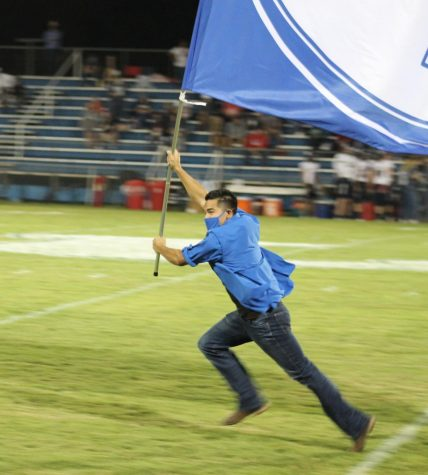 Senior Xavier Gauna runs the Badger flag across Badger Stadium after a touchdown against Wimberly Sept. 11. The Badgers will play the Burnet Bulldogs tonight in Burnet.