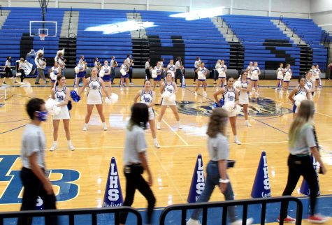 The band enters the gym with empty bleachers as the cheerleaders perform to record the first virtual pep rally Sept. 30. The pep rally will be shown tomorrow during academic period.