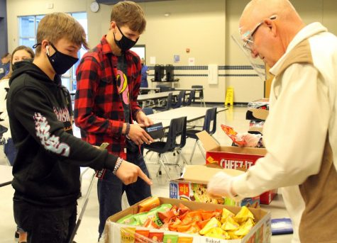 Students buy snacks from principal Joey McQueen during their designated day to mingle in the cafeteria during academic period.