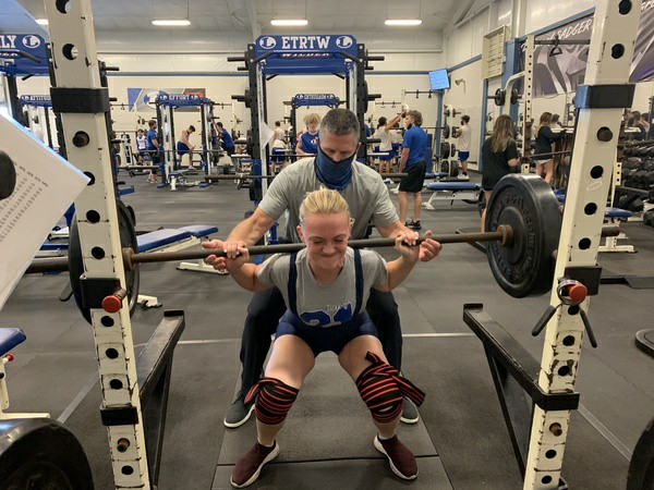Senior Madelyn Hess squats at powerlifting practice with coach Duane Young Dec. 14.