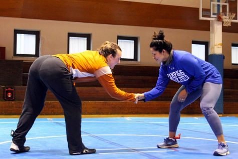 Senior Mia Martell and head wrestling coach Elma Garnett play a wrestling game at the first practice of the season Jan. 19.
