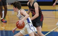 Junior Nate Borchardt dribbles the ball during a basketball game. The team begins their district season tonight.
