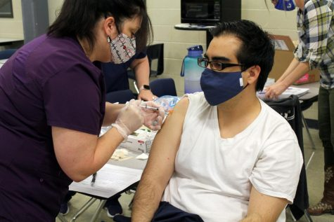 High school nurse Rhonda Hamilton administers the Moderna COVID-19 Vaccine to English teacher Nathaniel Brayton at the staff vaccination clinic March 10.