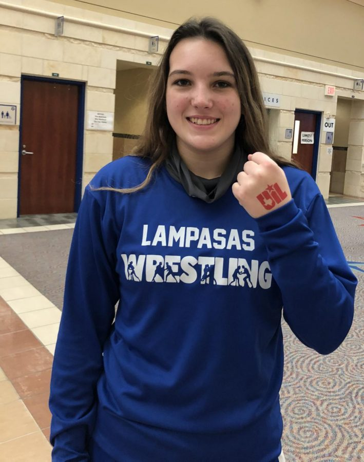 Senior Mia Martell shows off her participant stamp at the UIL State Wresting Meet.