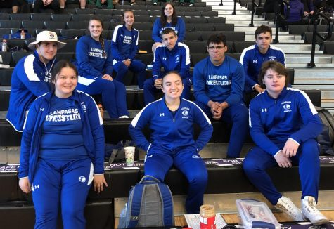 The varsity wrestling team sits together at the District meet in College Station April 9.