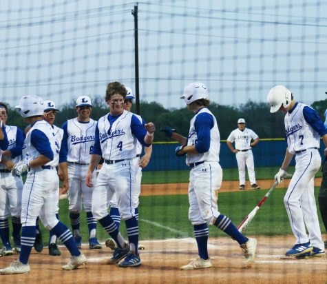 Senior Ace Whitehead fist bumps senior Guage Gholson after hitting a home run in the Badger