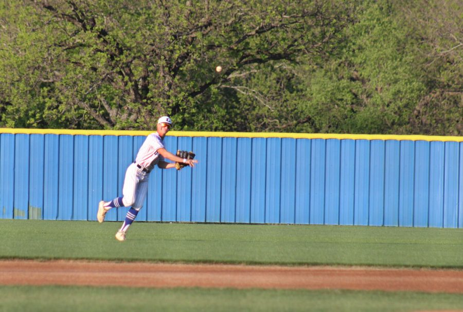 Senior Kash Corbin throws the baseball to warm up before the game April 20.