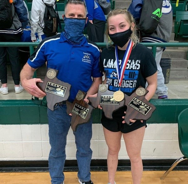 Girls powerlifting coach Duane Young and senior Alyssa Ayers hold Ayers awards from the State Powerlifting meet March 19.