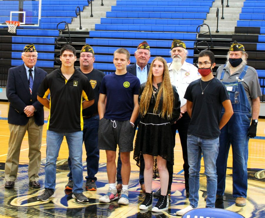 The seniors joining the military stand with members of Lampasas VFW during the signing ceremony.