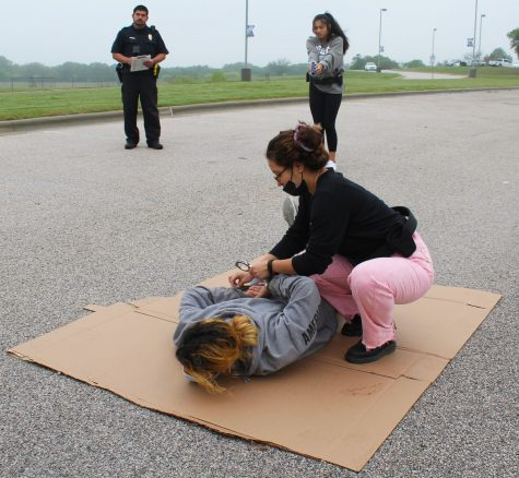 Senior Victoria  Garza puts handcuffs on sophomore DJ Ramirez during the felony traffic stop simulation for the tactical competition April 23. Sophomore Amore Zapata assists in the the background while Officer Hernandez monitors and judges for the contest.
