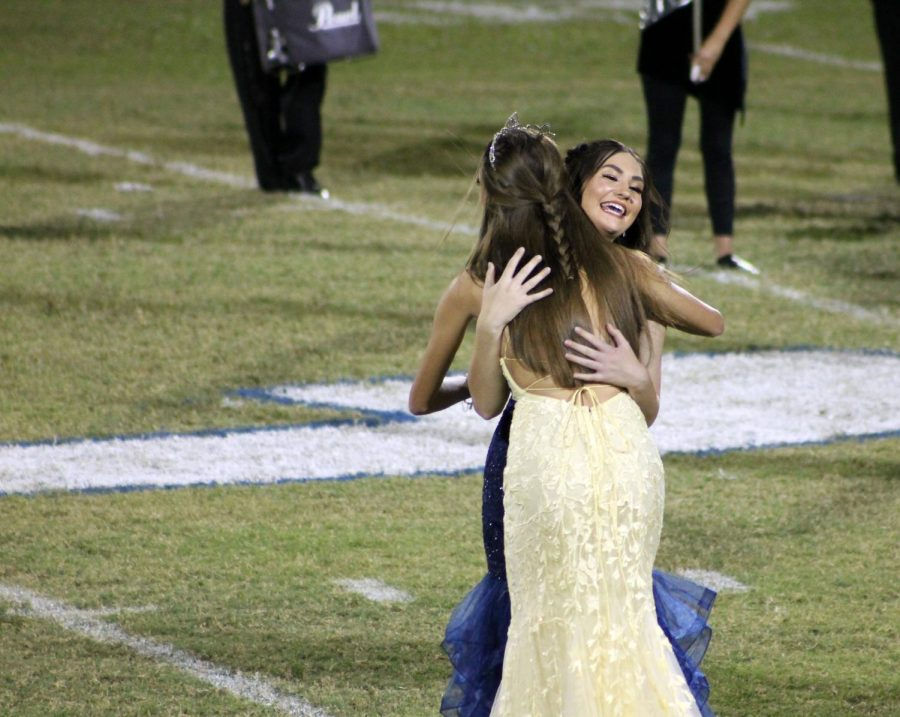 2021 homecoming queen Jara Stephens hugs 2020 homecoming queen Addison McDonald when she learns she won during the football game Sept. 17.
