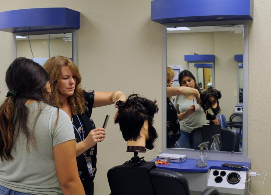 Cosmetology teacher Christine Hearn assists senior Isabella Guerra with a mens haircut.