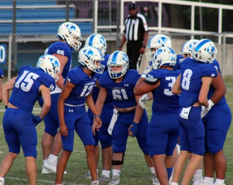 Varsity football players huddle between plays during the game on Sept. 17.