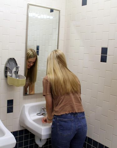Senior Kaylan Rucker washes her hands next to an empty soap dispenser. Custodians have not refilled the soap because it continues to be stolen due to the devious lick TikTok trend.